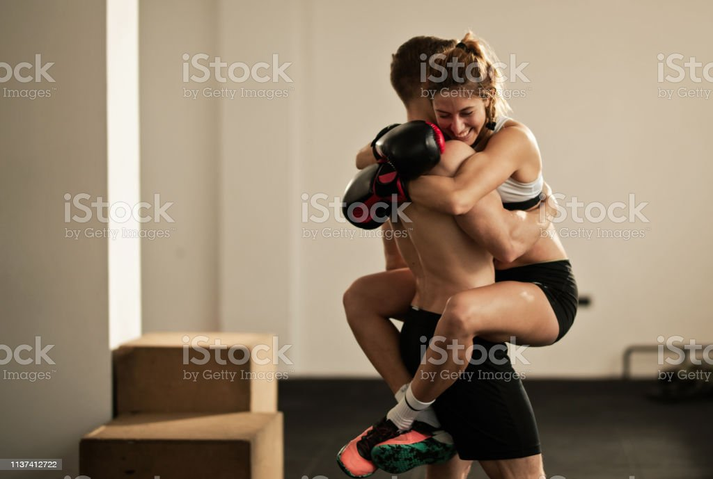 Happy female boxer embracing her personal instructor after sports...
