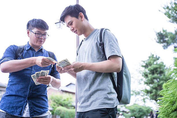 Thank you for lending me the money Student returning borrowed funds to his friend. borrowing stock pictures, royalty-free photos & images