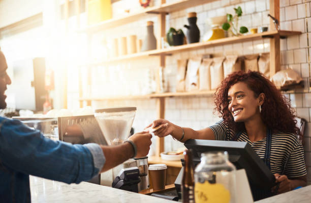 Thank you for stopping by the best cafe in town Shot of a waitress accepting a credit card payment from a customer in a cafe barista stock pictures, royalty-free photos & images