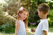 Cute little girl happy to receive a flower from a boy