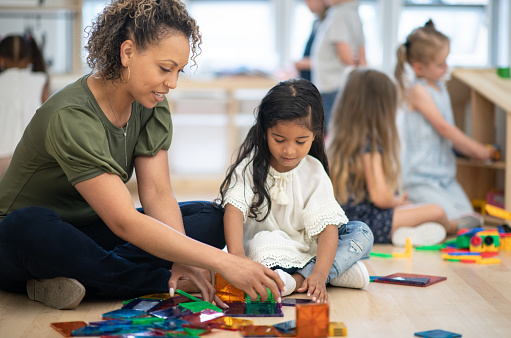 A female preschool teacher of African ethnicity helps one of her students build a tower using magnetic tiles.