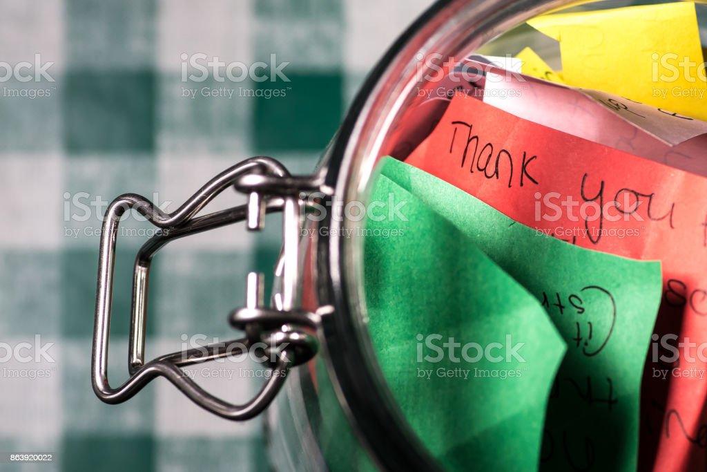 Merci jar avec les messages écrits sur papier de couleur - Photo