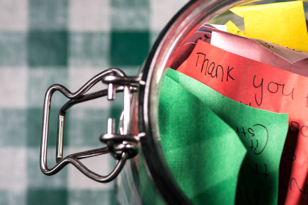 Thank you jar with messages written on coloured paper stock photo
