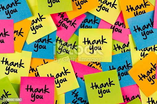 Thank you sticky note with multiple colored adhesive notes on bulletin board