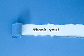 istock Thank you message under blue torn paper. 851098560