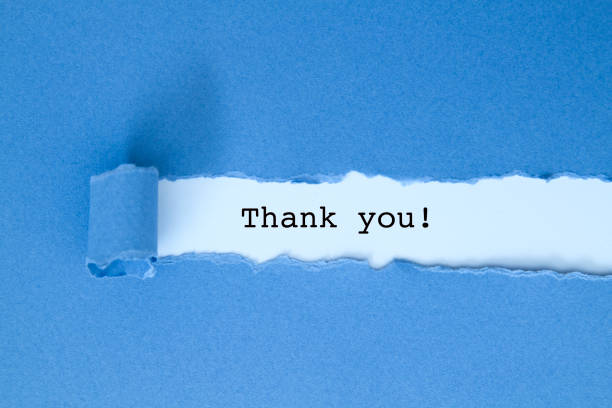Thank you message under blue torn paper. stock photo