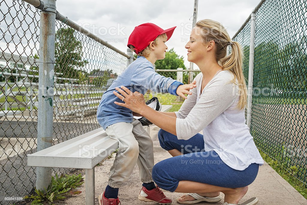 Thank you Mom! Mother and son hugging on baseball bench. stock photo