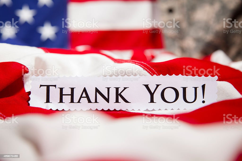 'Thank You' note in front of American flags, military uniform. stock photo