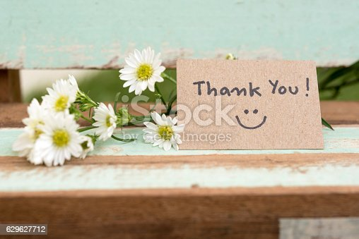 istock Thank you note with smile face and flower cluster 629627712