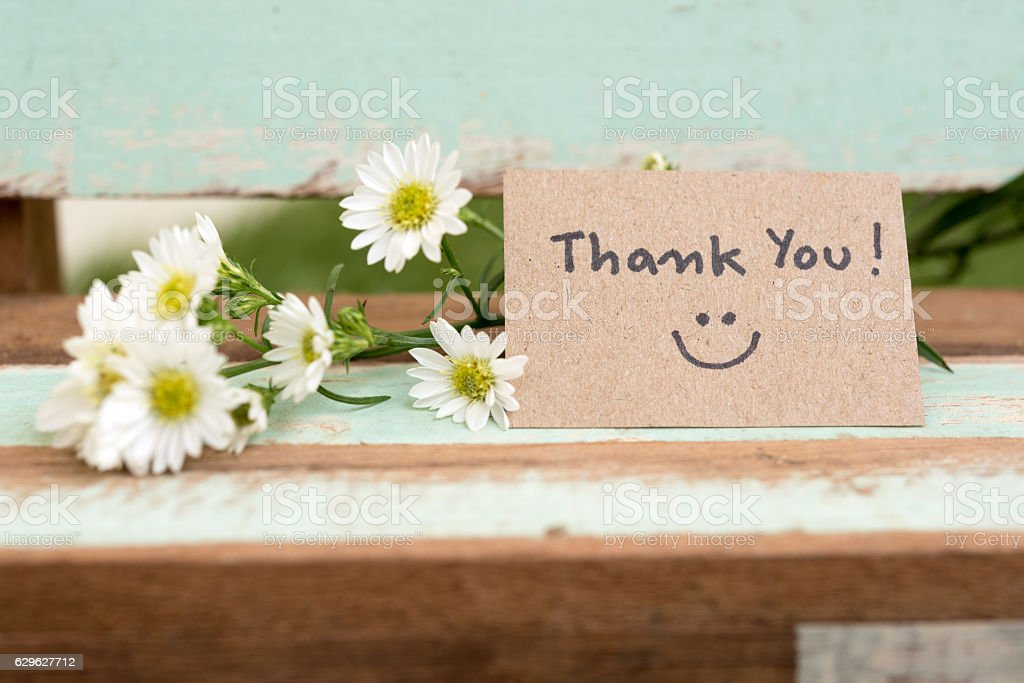 Thank you note with smile face and flower cluster stock photo
