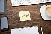 High Angle View Of Text Thank You On Post Note At Wooden Desk