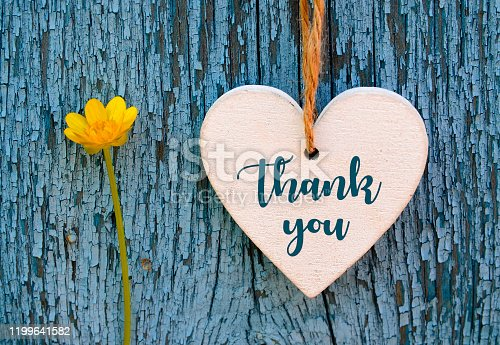 Thank You or thanks greeting card with yellow flower and decorative white heart on blue wooden background. International Thank You Day concept.Selective focus.