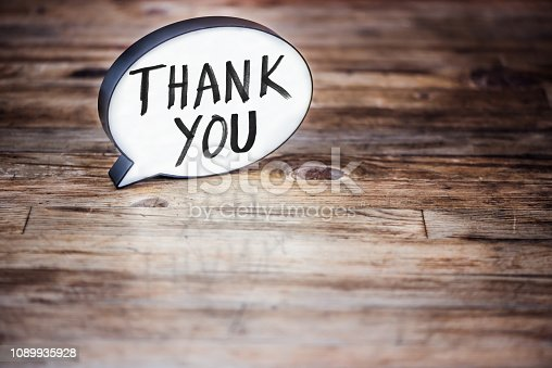 Lightbox in form of a Speech bubble on wood desk showing the word Thank you.