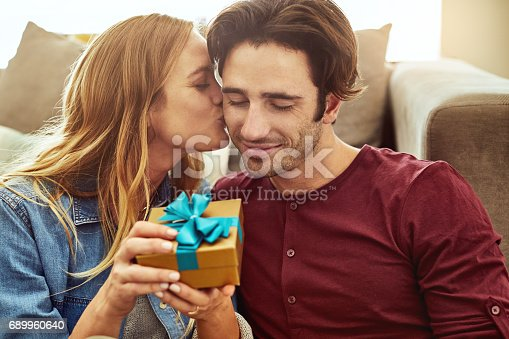 Cropped shot of a young woman kissing her boyfriend in gratitude while holding a gift