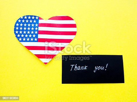 istock Thank you sign on a chalkboard with American flag on yellow background, USA 963190994