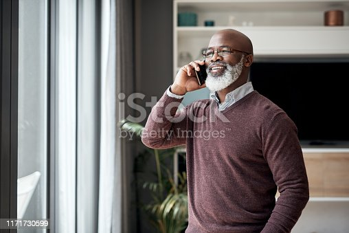 Cropped shot of a happy senior man standing alone in his living room at home and using his cellphone