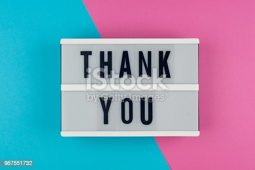 istock Thank you - text on a display lightbox on blue and pink bright background. 957551732