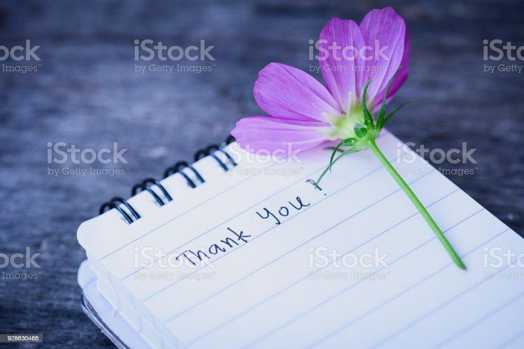 Danke Text auf einer weißen Seite Notizbuch mit romantische weiße Blume auf hölzernen Hintergrund. – Foto