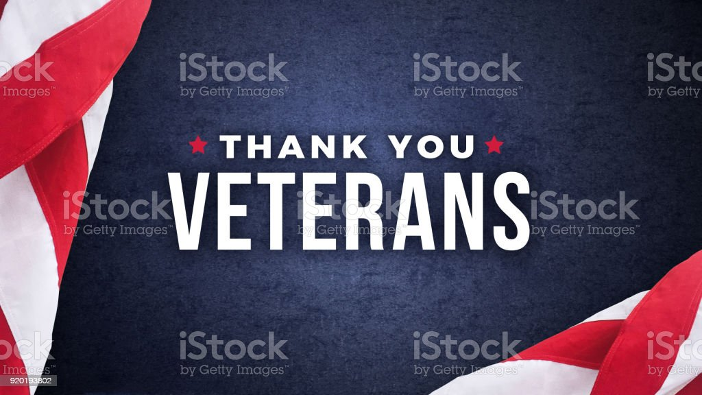 Thank You Veterans Text with American Flags Over Dark Blue Background stock photo