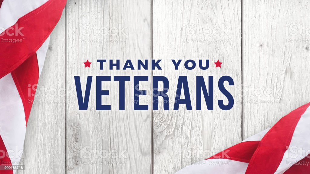 Thank You Veterans Text with American Flags Over Wood Background stock photo