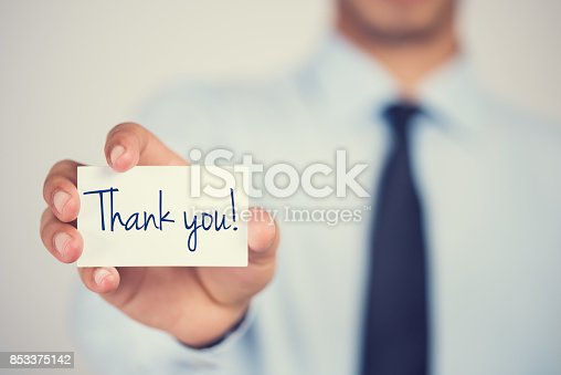 istock Thank you word on card hold by man 853375142