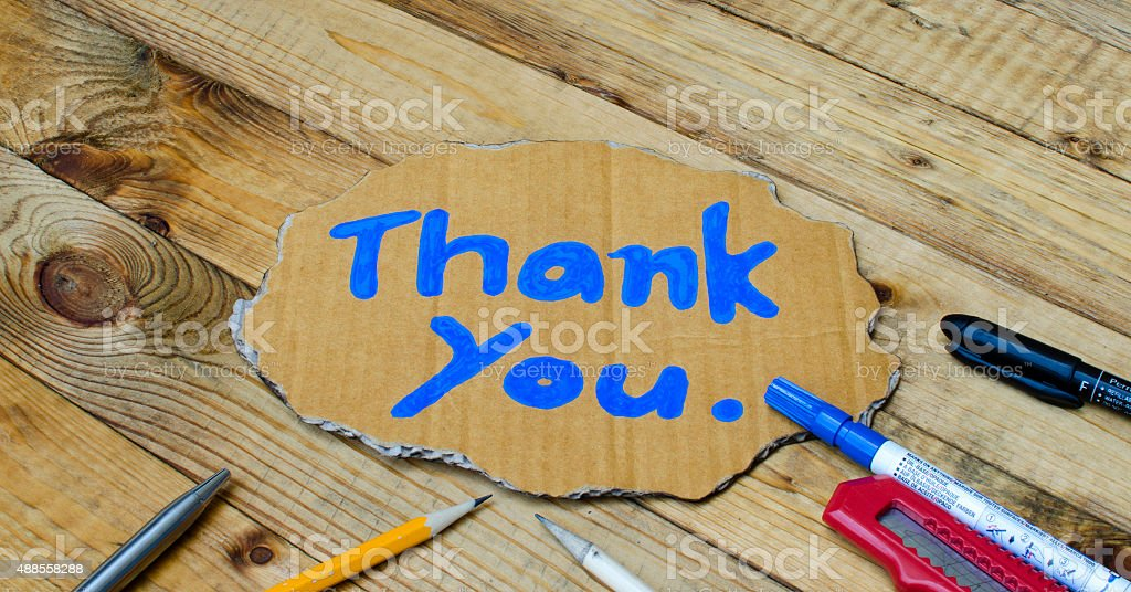 Thank you wording on cardboard on wooden background stock photo