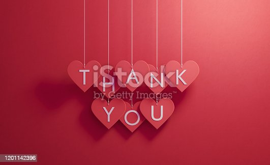Thank you writes over red heart shapes hanging over red background, Horizontal composition. Thank you concept.