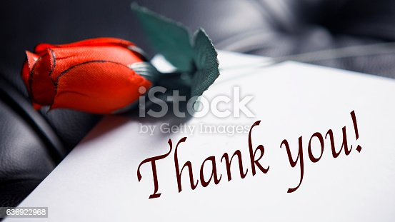 istock Thank You written on paper next to red rose 636922968