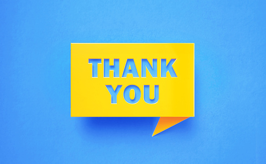 Thank you written yellow chat bubble on blue background. Horizontal composition with copy space. Gratitude concept.