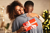 istock Thankful afro woman with christmas gift hugging husband at home 1181610754