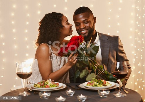 istock Thankful black lady holding bunch of roses, kissing her boyfriend 1201655671