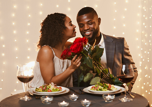 Thankful black lady holding bunch of red roses, kissing her happy man, having romantic date at restaurant