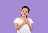 感謝の中国の女の子は紫色の背景の上に胸に手を押す