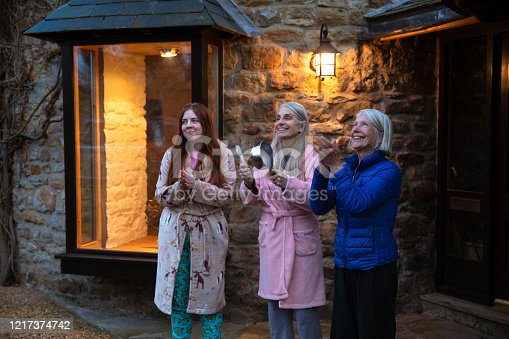 A multi-generation family in self isolation standing outside their home clapping and smiling together, one woman is using a pan to make noise. They are showing their support for all the workers and helpers who are helping during the COVID-19 outbreak.