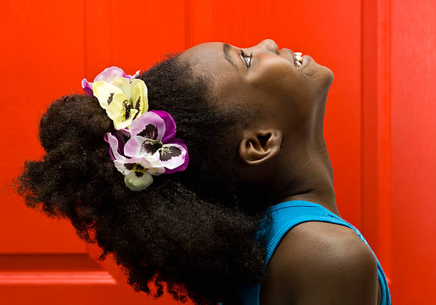 Thankful little girl african descent little girl looking up smiling daydreaming on red background  (this picture has been taken with a Hasselblad H3D II 31 megapixels camera)  haitian ethnicity stock pictures, royalty-free photos & images