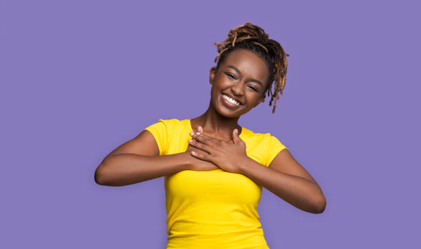 Thankful smiling african girl holding hands on her chest stock photo