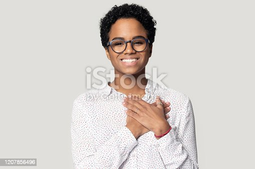 Sincere thankful smiling african american woman holding hands near heart on chest, looking at camera. Head shot close up portrait grateful woman in eyeglasses, isolated on grey studio background.