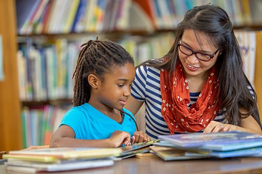 A female teacher of Asian ethnicity is helping her student with a book. They are at their school library.