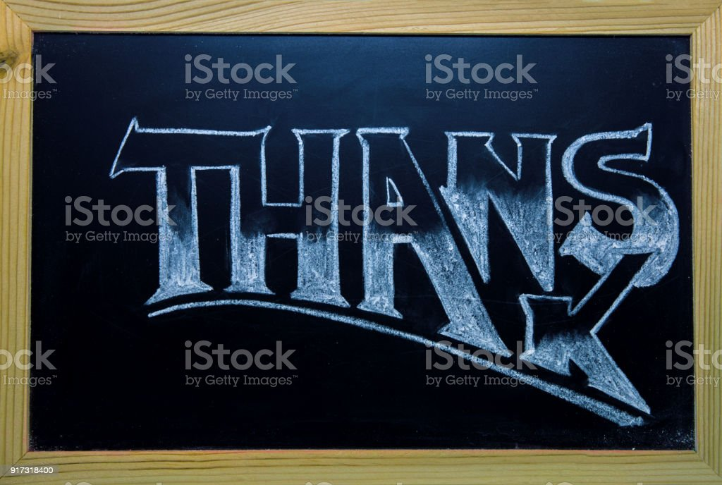 Thanks inscription by white chalk on black chalkboard. Thanks word in wooden frame stock photo
