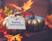 istock Thanksgiving background with metallic pumpkin, greeting and leaves 1035696234