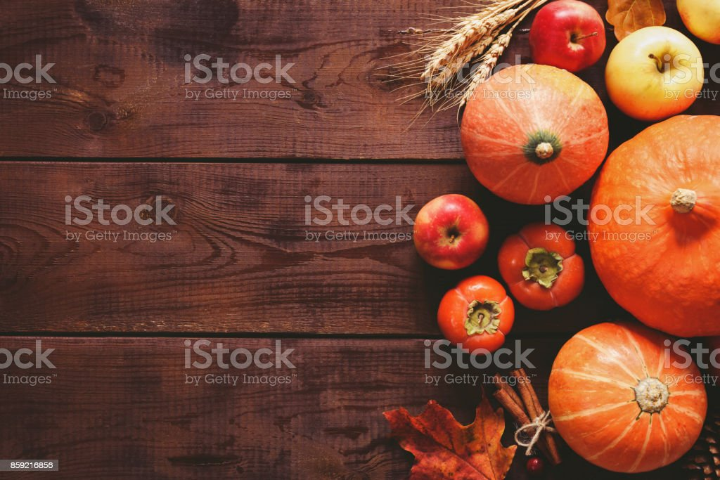 Thanksgiving background with pumpkins, apples and fallen leaves on wooden table stock photo