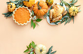 Thanksgiving dinner invitation concept or mock up, top down view on autumn traditional food decorated with pumpkins and sage