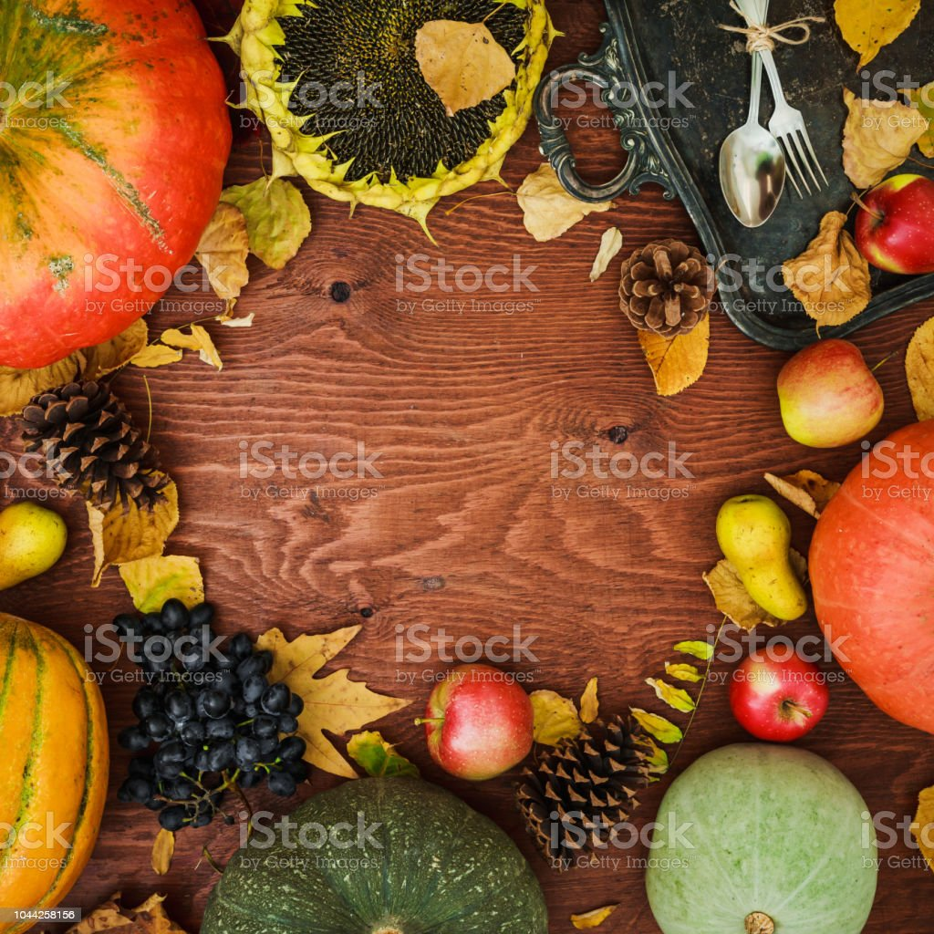 Thanksgiving day composition of vegetables, sunflower, apple and fall leaves on wooden background. Flat lay, top view. Dinner table stock photo
