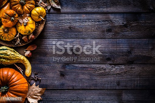 Top view of autumnal colorful pumpkins and fallen leaves placed at the left border of a rustic wooden table leaving useful copy space for text and/or logo. Predominant colors are orange, yellow and brown. Low key DSRL studio photo taken with Canon EOS 5D Mk II and Canon EF 100mm f/2.8L Macro IS USM.