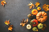 Thanksgiving day or seasonal autumnal background with pumpkins and fallen leaves