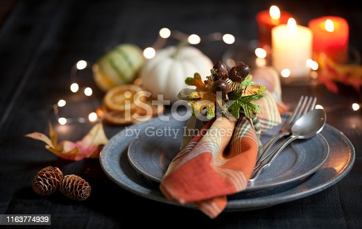 Elegant autumn Thanksgiving dining place setting on an old rustic wood table with candles.