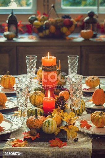 Autumn table setting for Thanksgiving dinner with candles, pumpkins and leafs