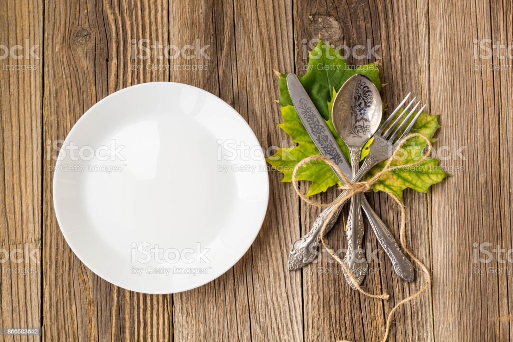 Thanksgiving Dinner Plate With Fork Knife And Autumn Leaves On Rustic Wooden Table Background