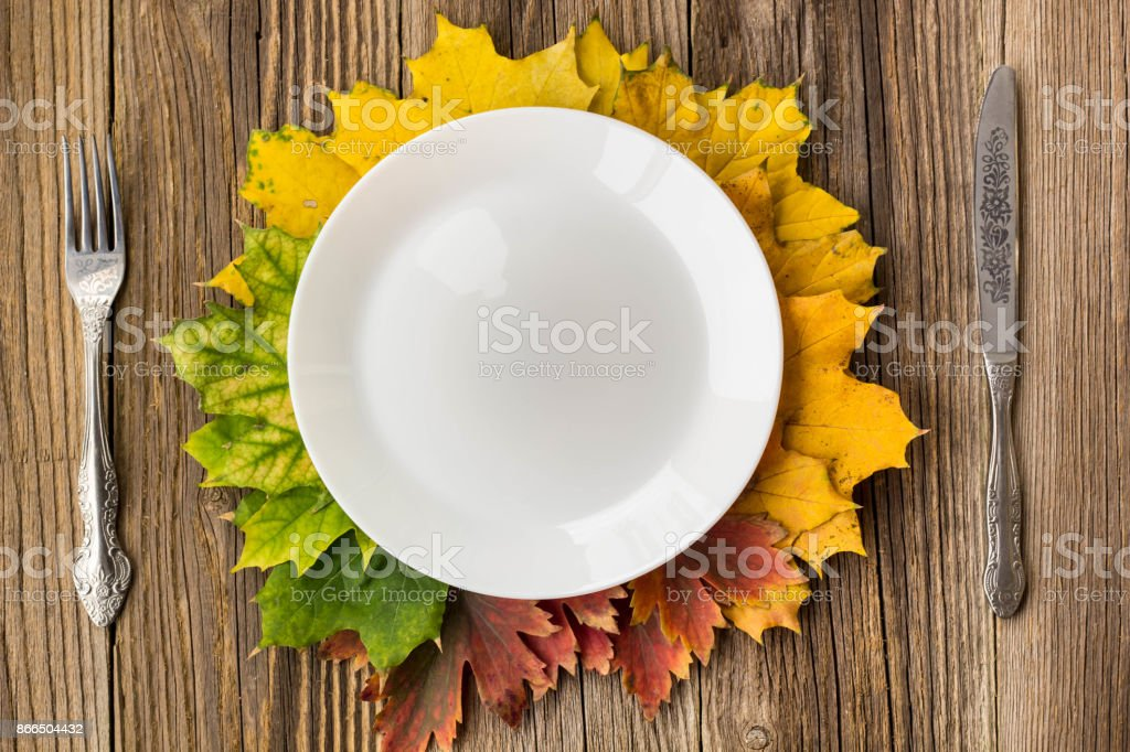 thanksgiving dinner plate with fork knife and autumn leaves on rustic picture id