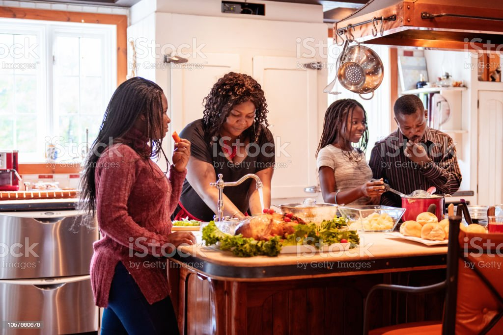 Thanksgiving dinner with American-African family preparing dinner stock photo